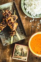 Grilled chicken skewers with rice and satay sauce (Asia)
