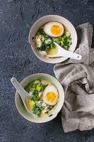 Two bowls with asian style soup with scrambled eggs, half of marinated egg, spring onion, spinach