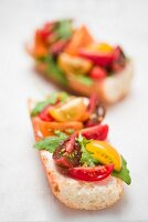 Baguette with cream cheese, various tomatoes and rocket