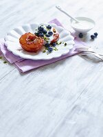Baked peach with Greek yoghurt, blueberries and pistachios
