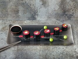 Quinoa sushi with smoked salmon, dyed in beetroot juice