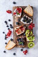 Verschiedene süss belegte Brote mit Frischkäse, Früchten und Schokosauce