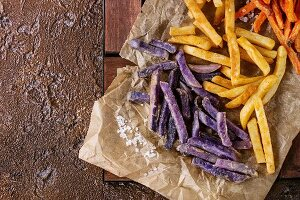 Variety of french fries traditional potatoes, purple potato, carrot served with salt on baking paper over brown texture background