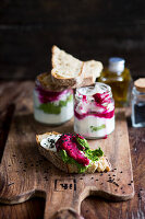 A slice of baguette topped with goat's cheese and beetroot