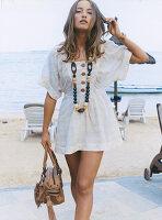 Junge Frau in weißem, kurzem Sommerkleid und mit Halskette am Strand