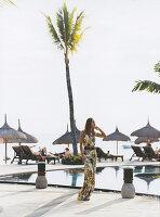 Junge Frau in langem, bedrucktem Sommerkleid am Strand