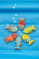 Fish shaped biscuits with colorful icing on a blue background