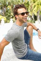 Junger Mann mit Sonnenbrille in grauem T-Shirt und Jeans-Bermuda