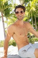 Junger Mann mit Sonnenbrille, nacktem Oberkörper und Shorts