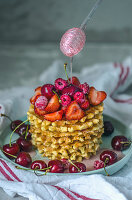 Stacked waffles with berries, cherries and honey