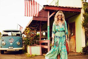 Junge Frau in langem Sommerkleid in Grüntönen