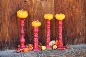 Kleine Speisekürbisse auf Kerzenhaltern