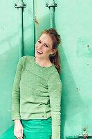 Junge Frau in grünem Pullover und grüner Hose vor grünem Hintergrund