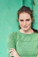 Junge Frau in grünem Pullover vor grünem Hintergrund