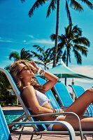 Junge Frau im Bikini sitzt im Liegestuhl