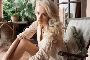 Blonde, langhaarige Frau in hellem Kleid