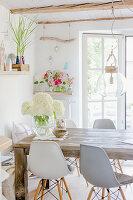 Weiße Hortensien auf rustikalem Holztisch, darüber Pendelleuchte mit Glasschirm und Klassikerstühle im Esszimmer