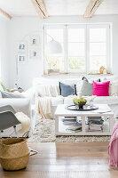 Wohnzimmer im Landhausstil mit weißen Hussenmöbeln und Couchtisch