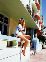Junge blonde Frau in weißem Bikini und mit JAcke sitzt auf Mauer