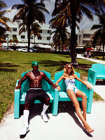 Junge blonde Frau im Badeanzug sitzt mit einem Mann in Shorts auf Stühlen