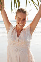 Blonde Frau in weißem Kleid mit Stickerei am Meer