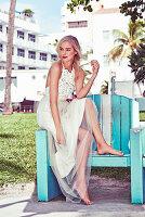 Junge blonde Frau in einem weißen Brautkleid auf Parkbank