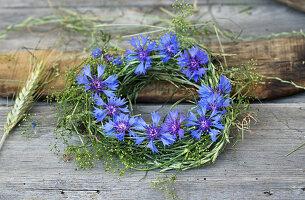 Kranz aus Gräsern und Labkraut mit Blüten von Kornblumen