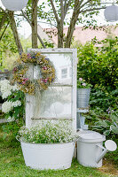 Getrockneter Blütenkranz an Fensterflügel, Zauberschnee in Zinkwanne