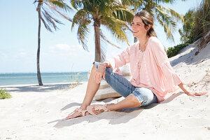 Brünette Frau in weiter Tunika und Jeans-Caprihose am Strand