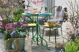 Kleine Sitzgruppe auf Osterterrasse mit Frühlingsblumen