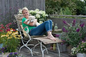 Balkon mit Sonnenhut Conetto 'Banana' 'Raspberry' 'Butterfly Kisses', Strauchhortensie, Eisenkraut, Sommerflieder, Frau auf Liegestuhl mit Hund Hera
