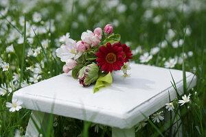Kleiner Strauß mit Apfelblüten, Papageientulpe und roten Margeriten auf Beistelltisch in der Wiese