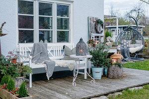 Terrasse mit Tannenbaum, Windlichtern und Bank mit Decke, Fell und Kissen