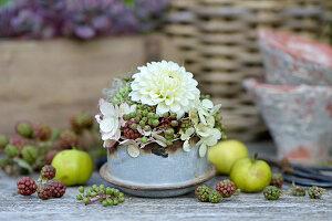 Herbstliches Gesteck mit Dahlie, Hortensienblüten und unreifen Beeren