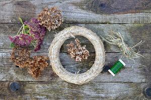 Zutaten für Herbstkranz: getrockneten Hortensienblüten, Fetthenne, Strohrömer, Heu und Bindedraht
