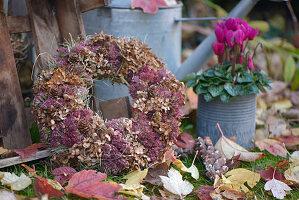 Herbstkranz aus getrockneten Hortensienblüten, Fetthenne, Zapfen und Heu