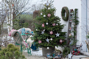 Nordmanntanne geschmückt mit Sternen und Kugeln als Weihnachtsbaum auf der Terrasse, kleine Sitzgruppe, Stühle mit Fell