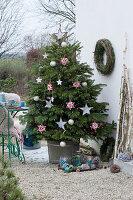 Nordmanntanne geschmückt mit Sternen und Kugeln als Weihnachtsbaum auf der Terrasse