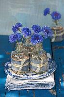 Kornblumen in kleinen Flaschen mit Deko