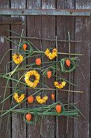 Wandbehang mit Rosen und Chinaschilf gestalten: Kränze aus Blütenblättern und Chinaschilf, Lampionfrüchte als Deko