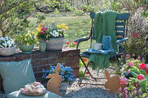 Kleine Kiesterrasse im Garten österlich mit Ostereiern und Holz-Osterhasen, Stuhl mit Decke, Tassen, Krug und Gläsern