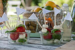 Mozzarella-Tomaten-Spieße in Gläsern, Flasche mit Holunderblütensirup