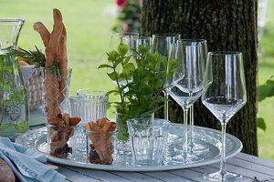Brotstangen, Gemüsechips, Strauß aus frischer Minze und Gläser auf Tablett
