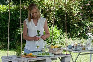 Frau gibt Orangenscheibe, Limette und frische Minze in Gläser, hängende Palette als Tisch