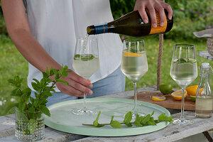 Frau füllt Gläser mit Prosecco, Strauß aus frischer Minze, Orangen, Limetten für Hugo
