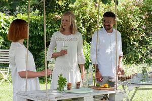 Freunde am hängenden Tisch aus weiß angemalter Palette