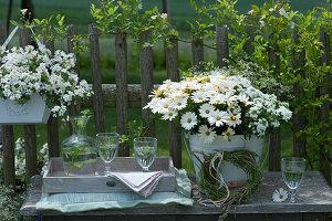 Willkommens-Arrangement mit Schneeflockenblume, Kapkörbchen, Verbene, Zauberschnee, Graskranz, Karaffe und Gläser auf Bank am Zaun