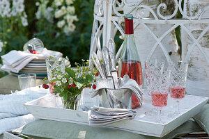 Weißes Tablett mit Strauß aus Walderdbeeren, Besteck und Servietten, Rosato in Flasche und Gläsern
