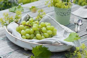 Weintrauben auf weißer Schale, mit Frauenmantel dekoriert