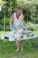 Weiße Palette als Sitzplatz mit Seilen an Baum gehängt, Frau schenkt Getränk ein